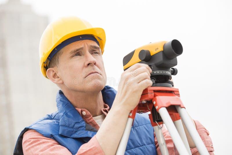 有经纬仪的测绘员在建造场所 图库摄影