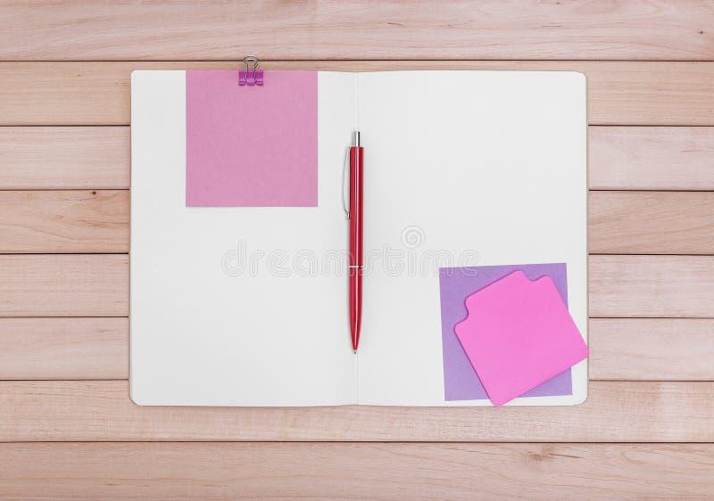 有贴纸的笔记本在木板背景  免版税图库摄影