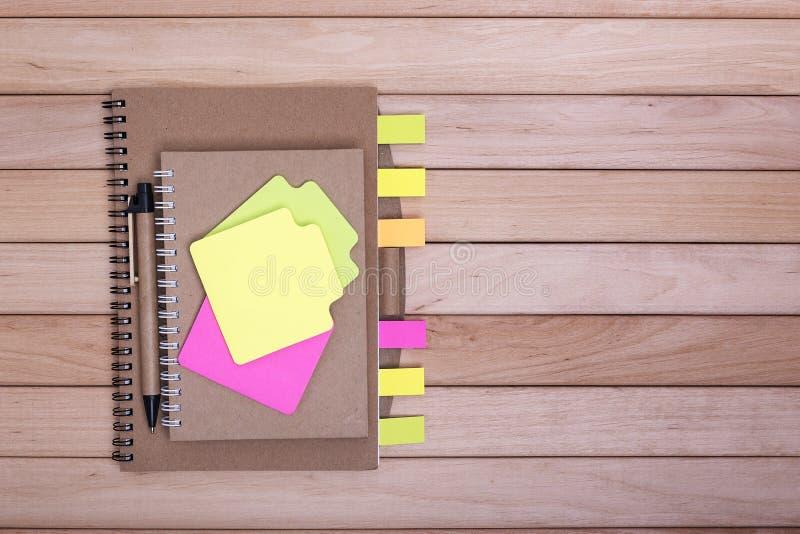 有贴纸的笔记本在木板背景  库存照片