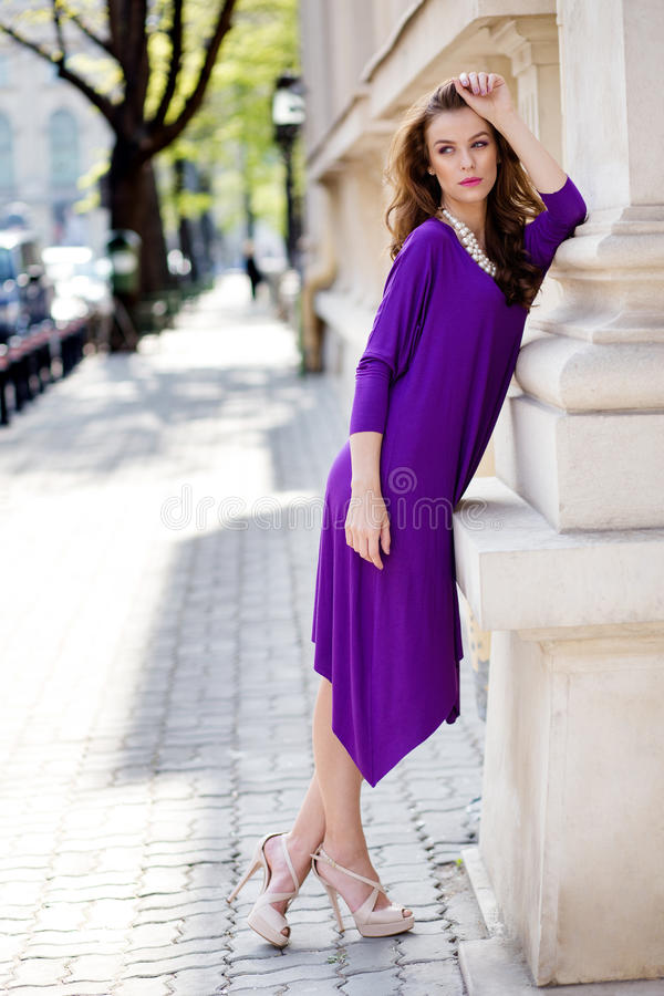 有紫罗兰色礼服的美丽的少妇 免版税库存照片