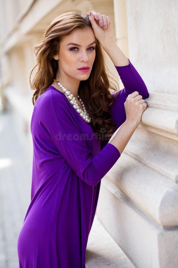 有紫罗兰色礼服的美丽的少妇 免版税图库摄影