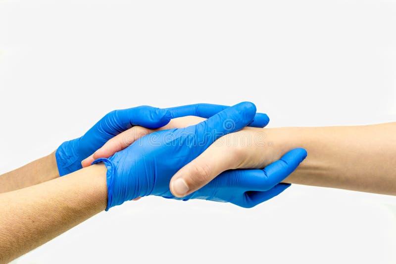有给舒适和握手的蓝色医疗手套的有同情心的手 库存图片