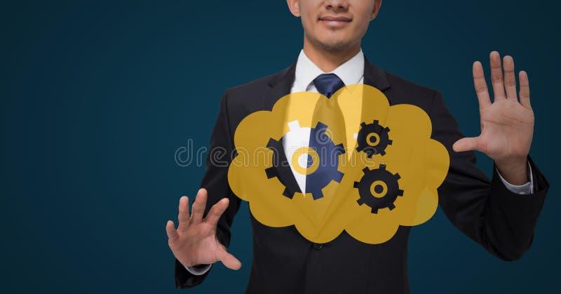 有黄色云彩和齿轮图表的商人在反对深蓝背景的手之间 库存照片