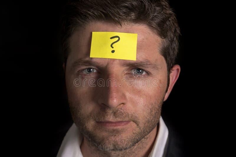 有黄色便条纸的人关于他的前额 库存图片