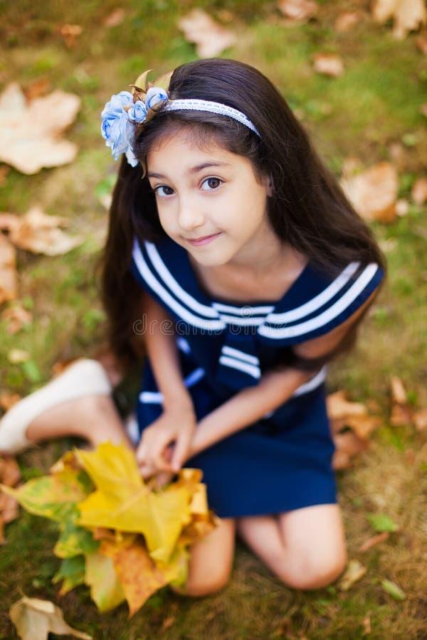 有黄色叶子的可爱的女孩 库存图片