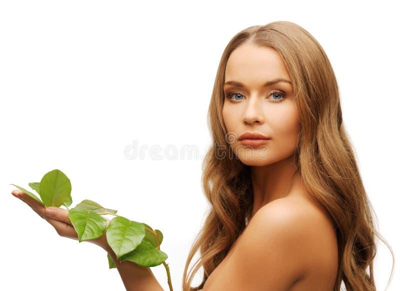 有绿色叶子的妇女 免版税图库摄影