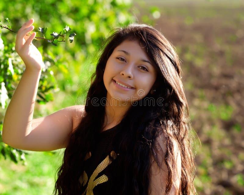 有绿色叶子的年轻微笑的妇女 免版税库存图片