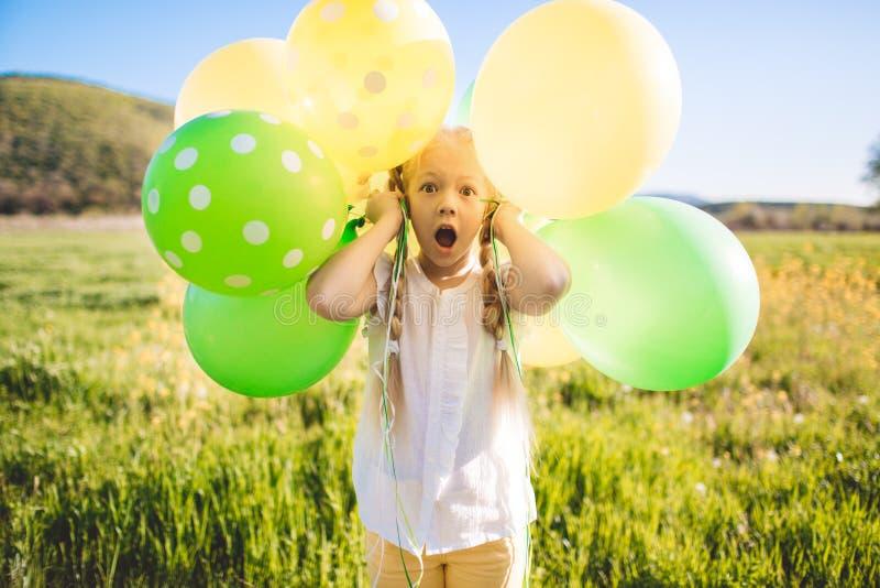 有绿色和黄色气球的小愉快的女孩 免版税库存照片