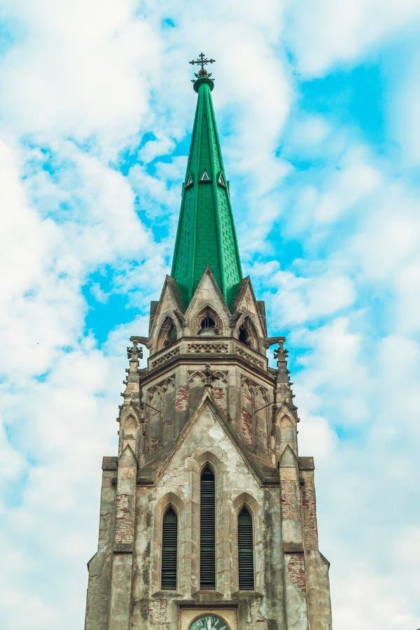 有绿色屋顶的,蓝天老历史大教堂,被定调子 库存图片