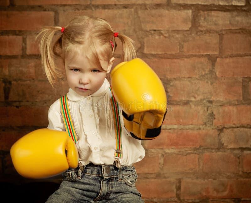 有黄色拳击手套的小女孩在砖墙 免版税库存图片