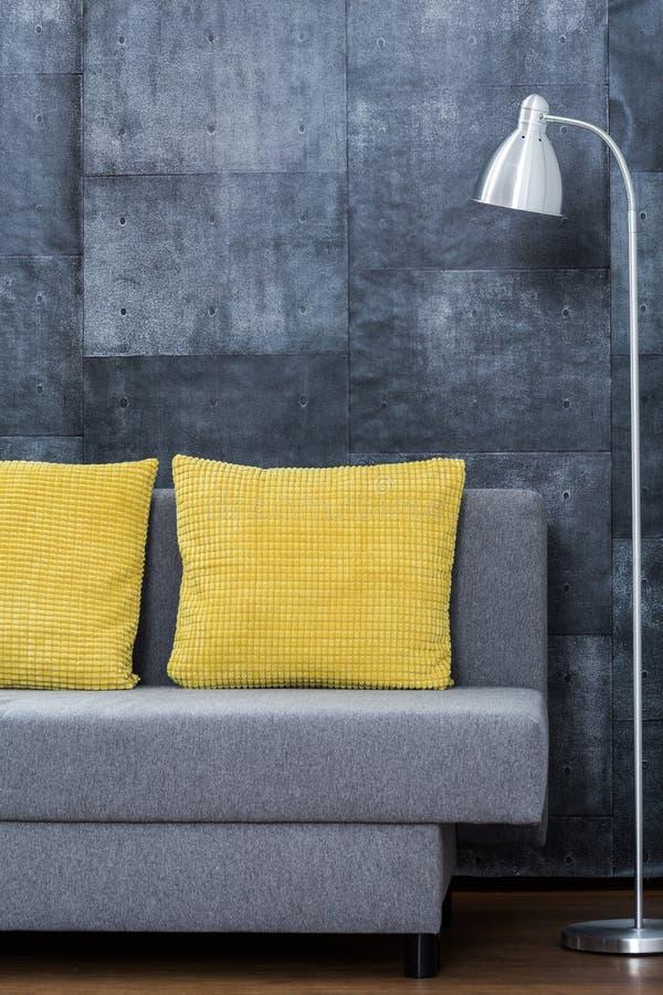 有黄色枕头的简单的沙发 免版税库存照片