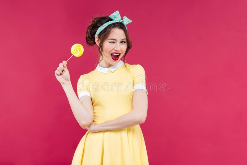 有黄色棒棒糖身分和w的快乐的迷人的画报女孩 免版税图库摄影