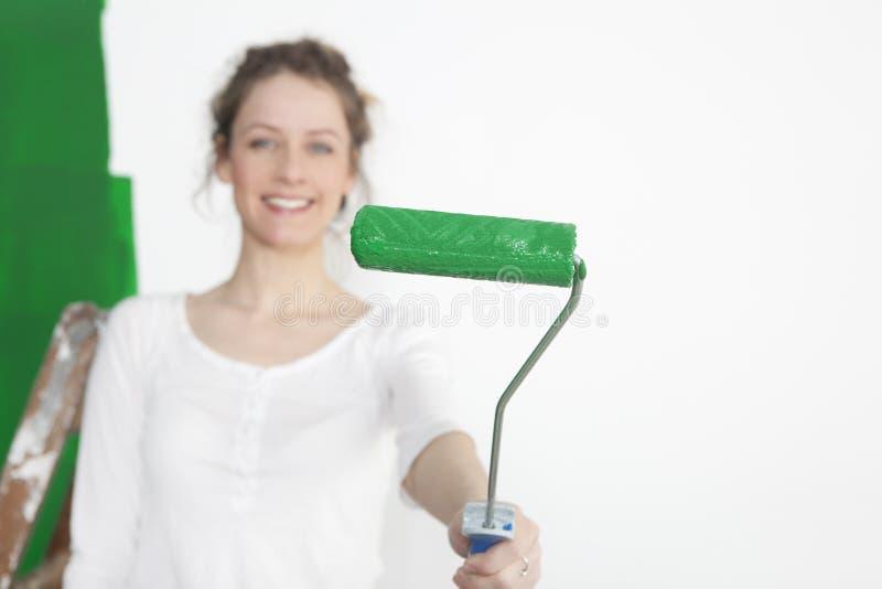 有绿色漆滚筒的妇女 免版税库存图片