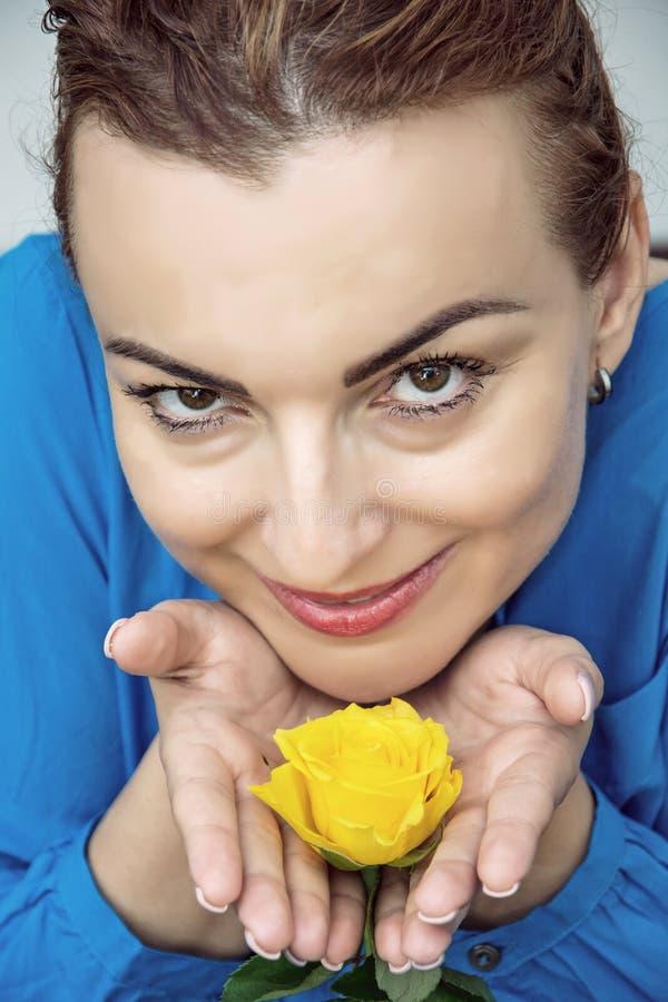 有黄色玫瑰的年轻可爱的白种人妇女在手上 图库摄影