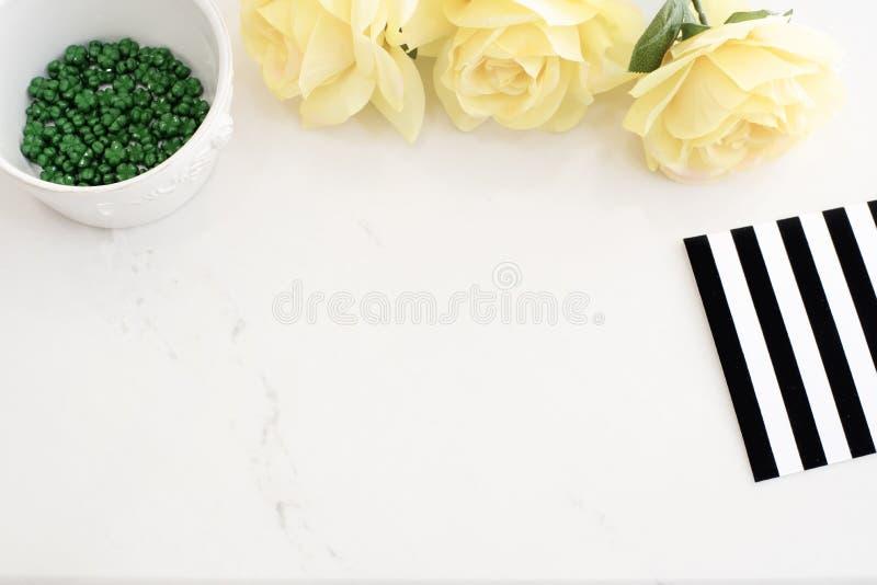 有黄色玫瑰的轻的大理石时髦的桌面,黑白色条纹设计 倒栽跳水网站或英雄网站,顶视图 空的地方, 库存照片