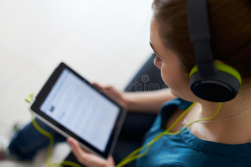 有绿色耳机的妇女听播客音乐片剂个人计算机 库存照片