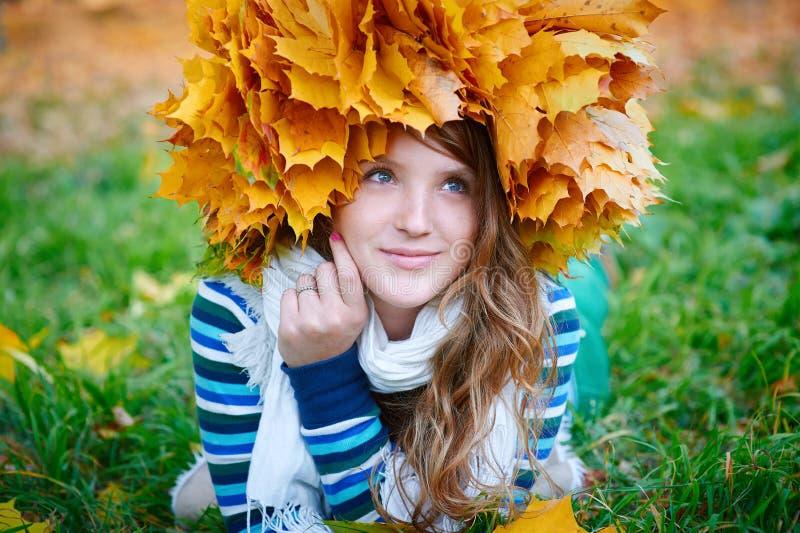 有黄色花圈的美丽的妇女在草留下说谎 免版税图库摄影