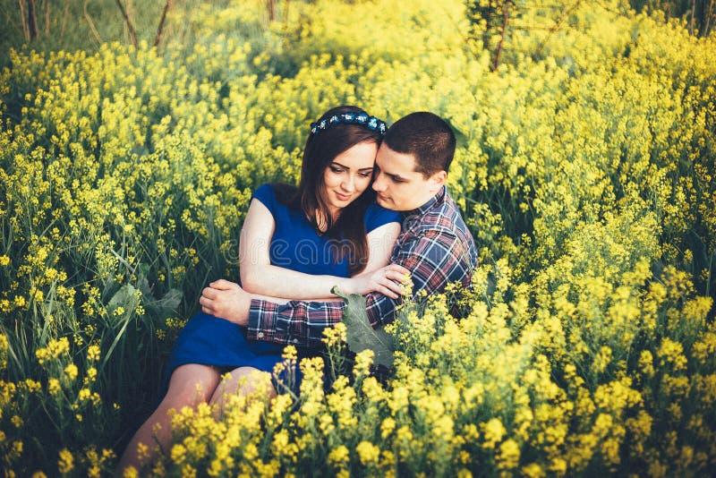 年轻有黄色花的夫妇坐的草甸 免版税库存照片