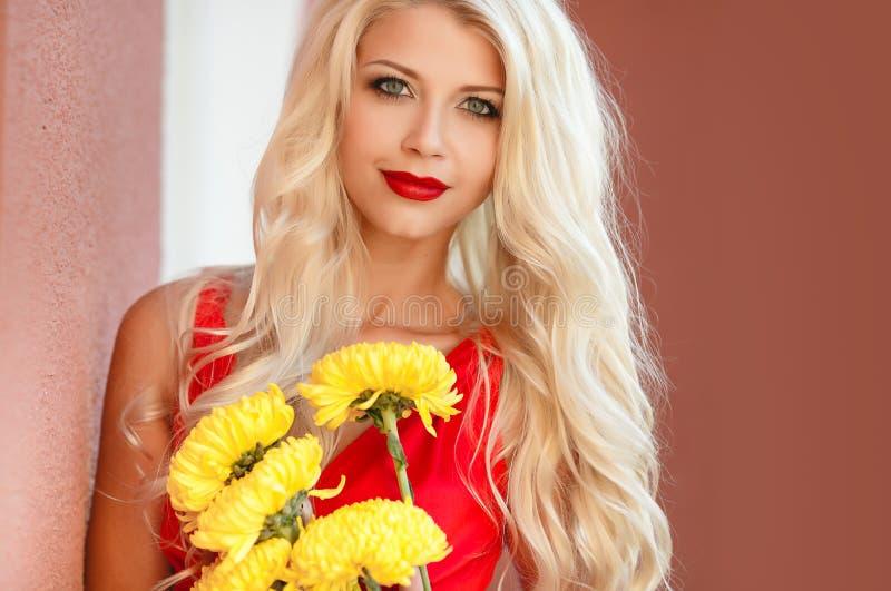 有黄色花花束的美丽的女孩  免版税库存图片