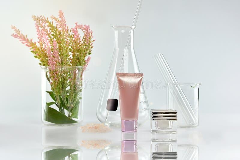 有绿色草本叶子和科学玻璃器皿的,烙记的大模型的空白的标签包裹化妆瓶容器 免版税库存图片