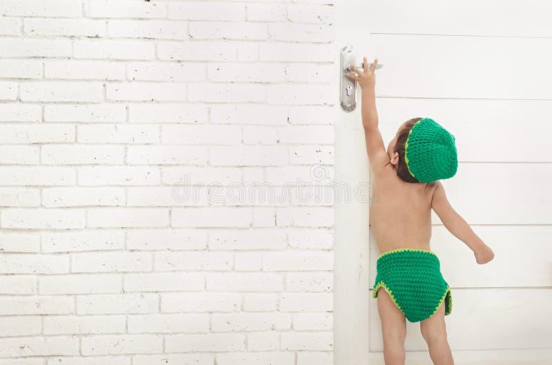 有绿色设法帽子和的裤子的小孩到达门把手 图库摄影