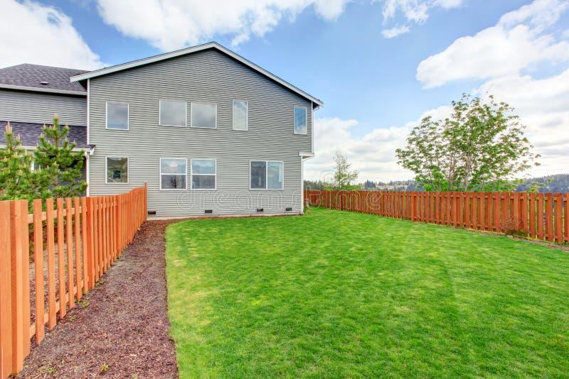 有绿草的宽敞被操刀的后院 一个大房子的议院外部 免版税库存图片