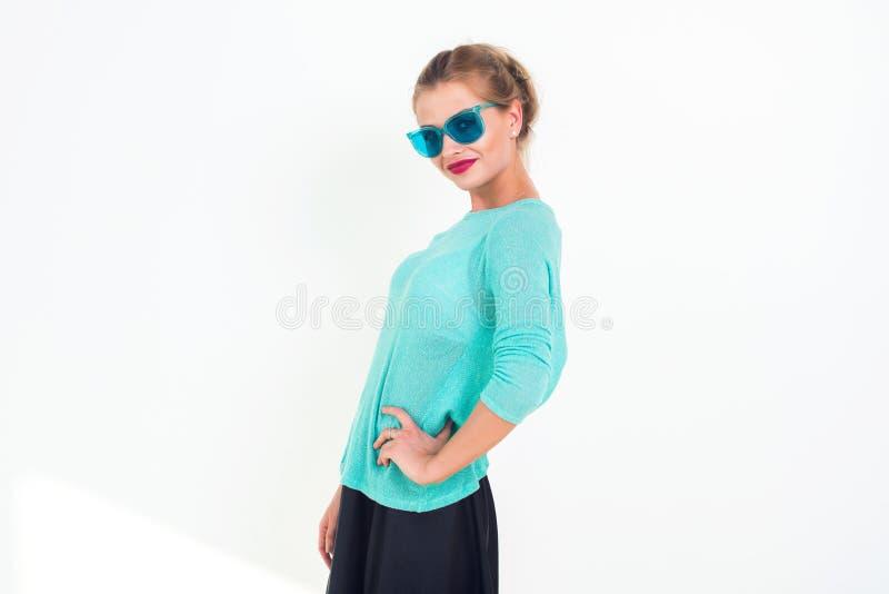 有戴蓝色太阳镜,有薄荷味的上面,摆在的一种美好的微笑和时髦的杂乱发型的女孩,站立 库存图片