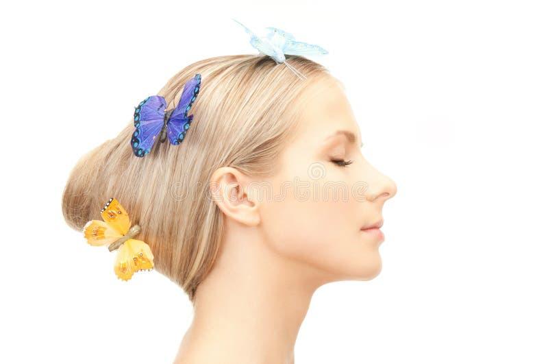 有蝴蝶的美丽的妇女在头发 免版税库存照片