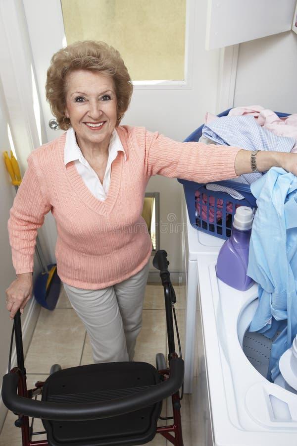 有洗衣店的资深妇女由洗衣机 库存图片
