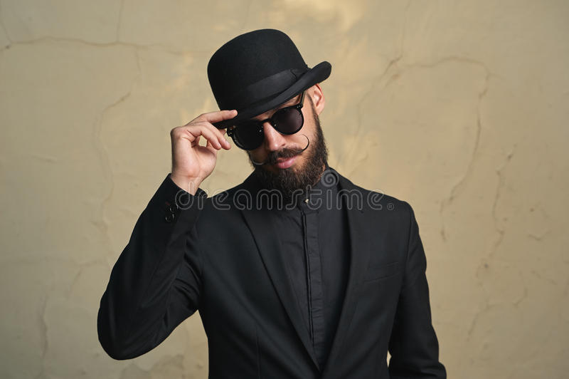 有黑衣裳的有胡子的人招呼 免版税库存照片