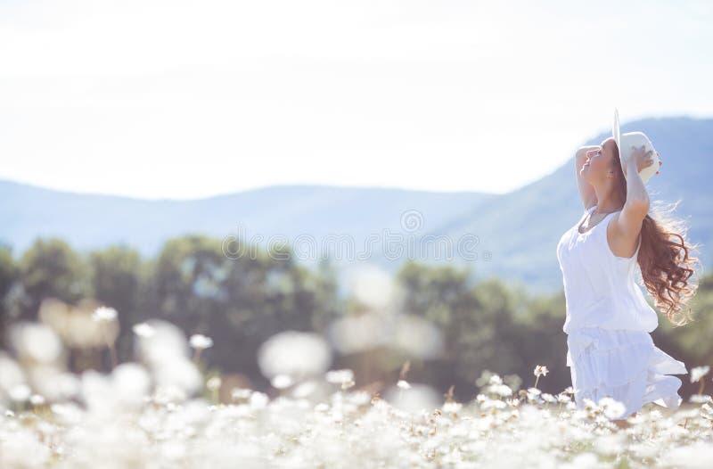 有戴西花束的一个少妇在草甸的 库存照片
