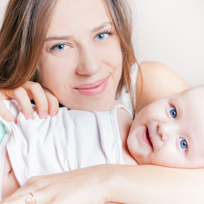 有说谎在一张白色床上的婴孩的愉快的母亲 免版税图库摄影