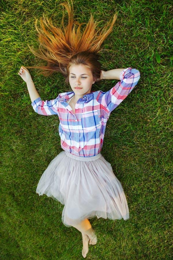 有说谎在格子花呢上衣和薄纱芭蕾舞短裙裙子的草的红色杂乱头发的白种人妇女 从上面上的看法 免版税库存照片