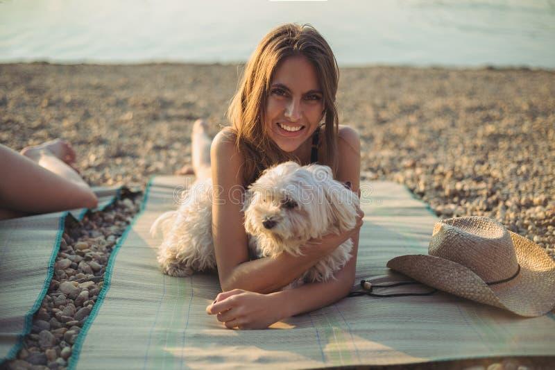 有说谎在海滩和微笑的狗的女孩 免版税库存图片