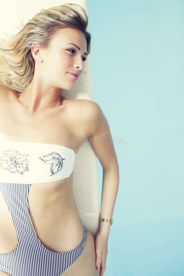有说谎在游泳池边缘的泳装的年轻白肤金发的妇女 免版税库存图片