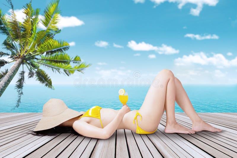 有说谎在码头的比基尼泳装的妇女 免版税图库摄影