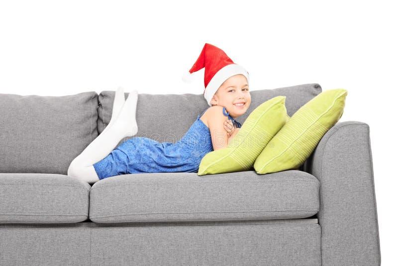 有说谎在长沙发的圣诞老人帽子的逗人喜爱的女孩 免版税库存图片