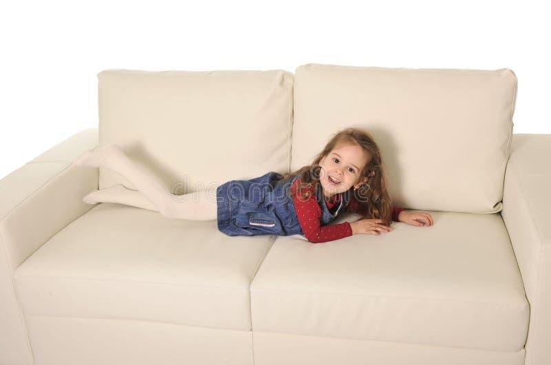 有说谎在长沙发的长的头发的愉快的可爱的小女孩嬉戏 库存照片