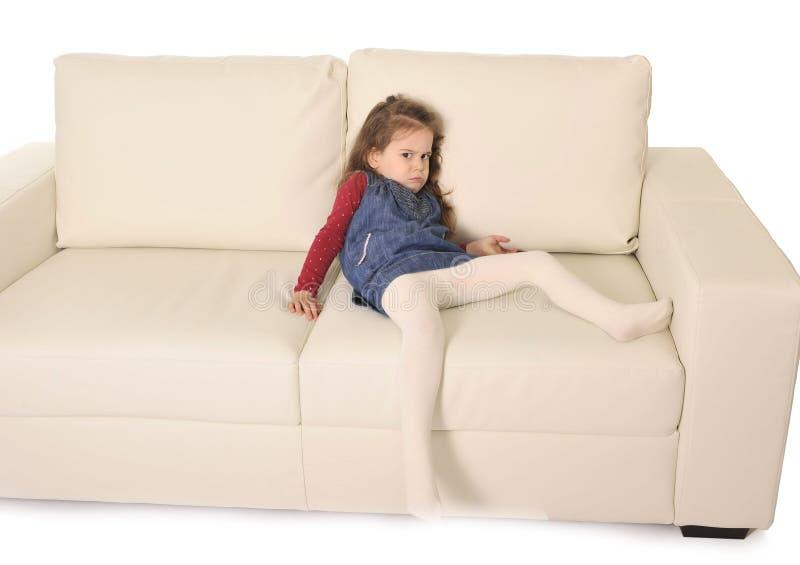 有说谎在长沙发的长的头发的愉快的可爱的小女孩嬉戏 免版税库存照片