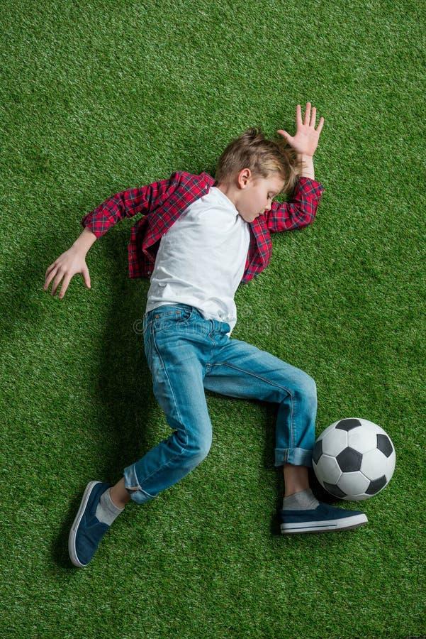有说谎在绿草的足球的男孩 免版税库存照片