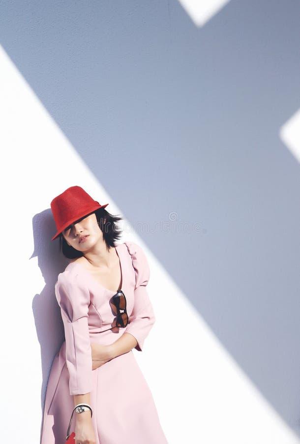 有说谎对墙壁的红色帽子的年轻亚裔妇女 免版税图库摄影