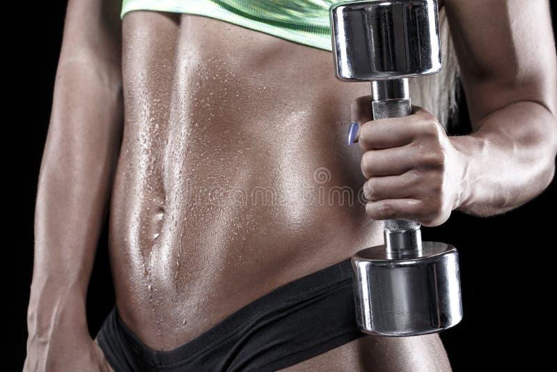 有满身是汗的身体锻炼的爱好健美者与哑铃 免版税图库摄影