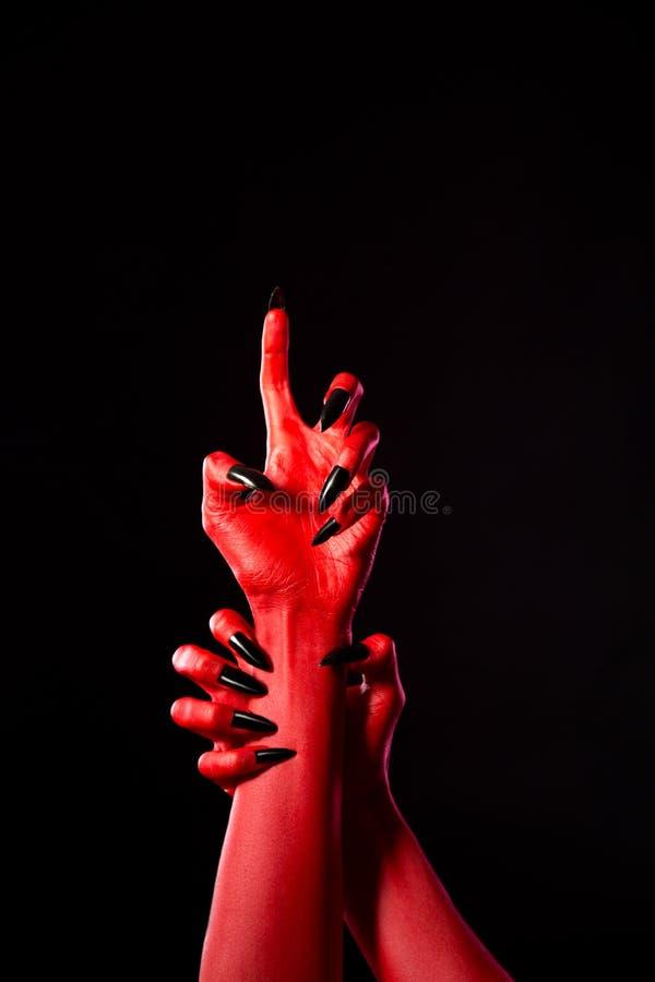 有黑钉子的可怕红色恶魔般的手,真正的身体艺术 免版税库存图片