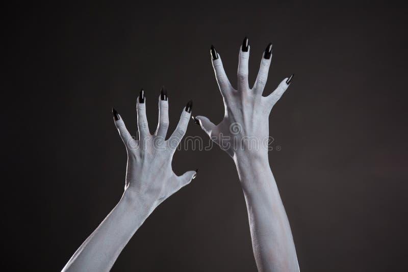 有黑钉子的恶魔般的手 免版税库存图片