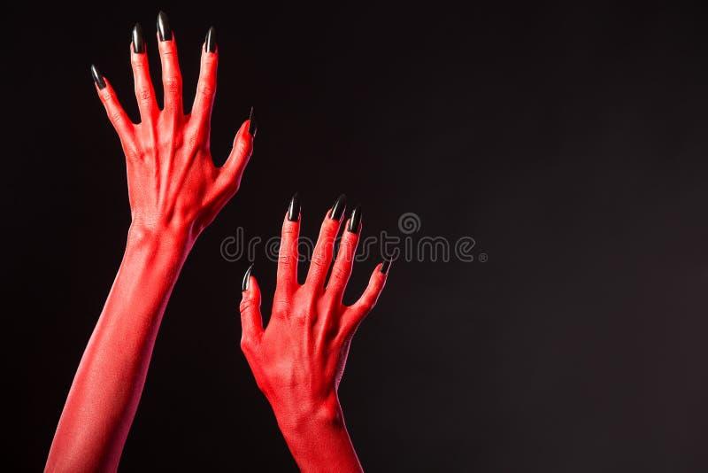 有黑钉子的红魔手,真正的身体艺术 库存图片