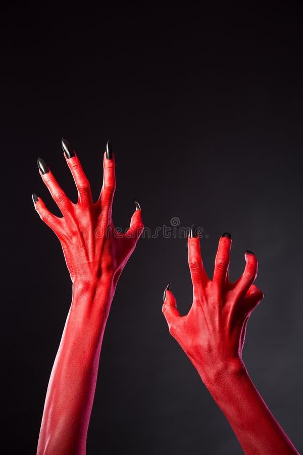 有黑钉子的红魔手,真正的身体艺术 免版税库存图片