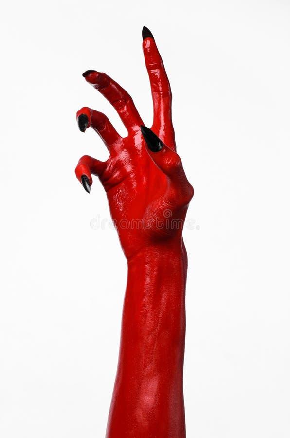 有黑钉子的红魔的手,撒旦,万圣夜题材的红色手,在白色背景,被隔绝 库存图片