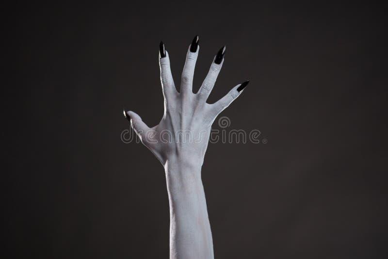 有黑钉子的鬼的白色手 库存图片