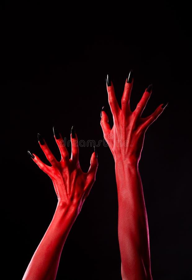 有黑钉子的鬼的红色恶魔般的手,真正的身体艺术 库存图片
