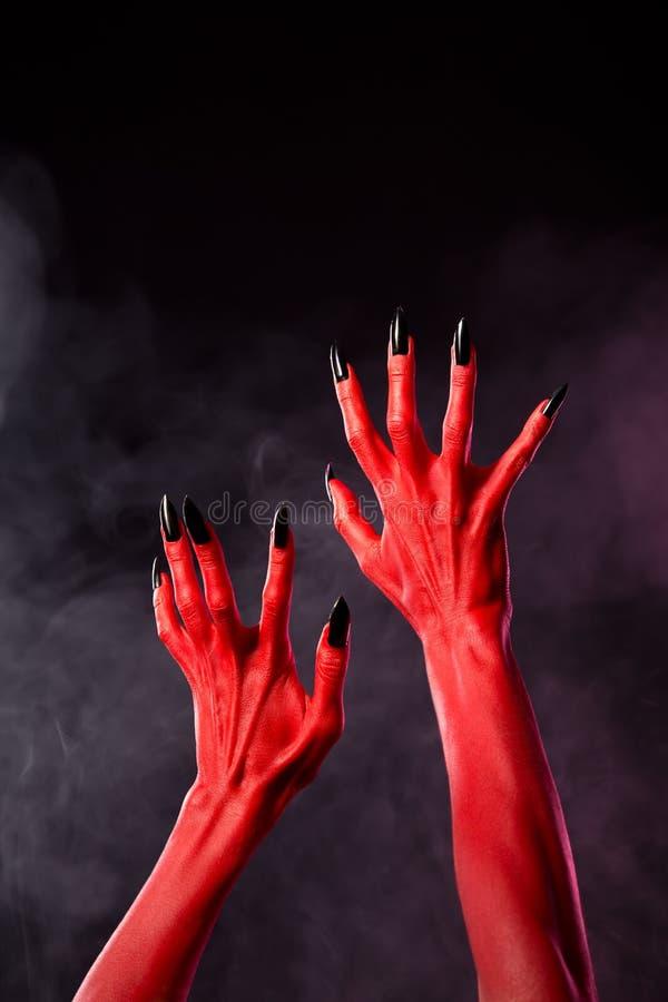 有黑锋利的钉子的红魔手,极端身体艺术 免版税库存图片